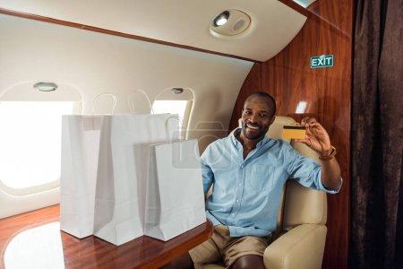 fröhlicher afrikanisch-amerikanischer Mann mit Kreditkarte und Einkaufstaschen im Privatflugzeug