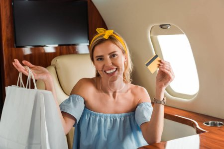 Photo pour Cheerful girl holding credit card and shopping bags in private plane - image libre de droit