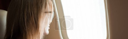 Photo for Panoramic shot of businesswoman in glasses looking at airplane window - Royalty Free Image