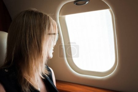 Photo for Businesswoman in glasses looking at airplane window - Royalty Free Image