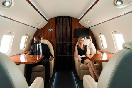 Photo for Selective focus of handsome african american businessman and attractive businesswoman sitting in private plane - Royalty Free Image