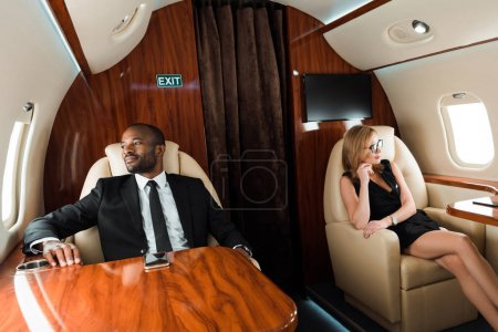 Photo for Selective focus of handsome african american businessman and beautiful businesswoman sitting in private plane - Royalty Free Image
