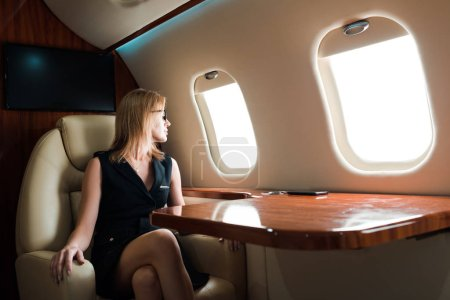 Photo pour Attractive businesswoman in glasses looking at airplane window in private jet - image libre de droit