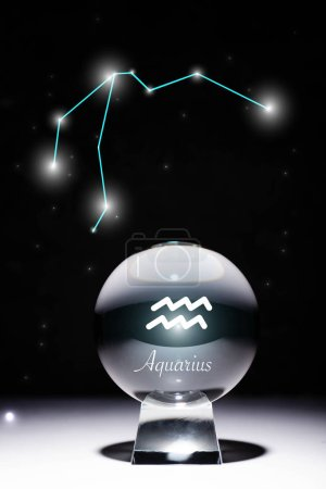 Photo pour Crystal ball with Aquarius zodiac sign isolated on black with constellation - image libre de droit
