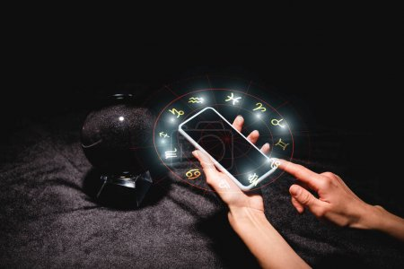 cropped view of astrologer holding smartphone with zodiac signs near crystal ball on black velvet cloth