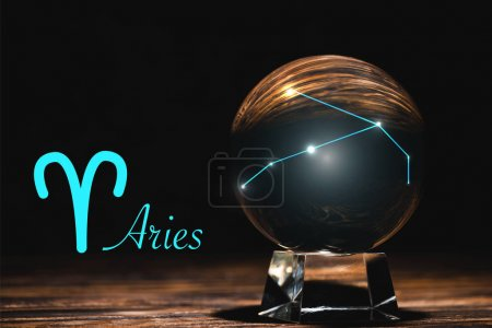 Photo pour Crystal ball with constellation near Aries zodiac sign on wooden table isolated on black - image libre de droit