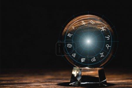 Photo pour Boule de cristal avec signes du zodiaque illustration sur table en bois isolé sur noir - image libre de droit