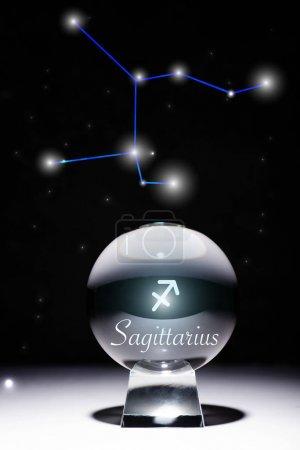 Foto de Balón de cristal con signo zodiaco Sagitario aislado en negro con constelación. - Imagen libre de derechos