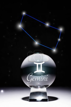 Photo pour Crystal ball with Gemini zodiac sign isolated on black with constellation - image libre de droit