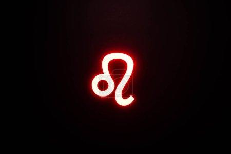 Photo pour Rouge illuminé signe du zodiaque Leo isolé sur noir - image libre de droit