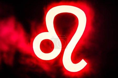 Photo pour Rouge lumineux signe du zodiaque Leo avec de la fumée sur le fond - image libre de droit