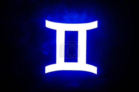 Photo for Blue illuminated Gemini zodiac sign with colorful smoke on background - Royalty Free Image