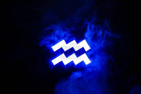 Photo for Blue illuminated Aquarius zodiac sign with smoke on background - Royalty Free Image