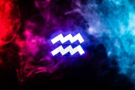 Photo pour Blue illuminated Aquarius zodiac sign with colorful smoke on background - image libre de droit