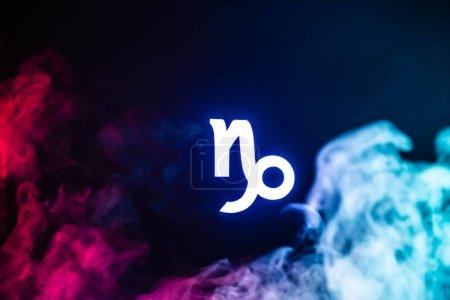 Foto de Signo zodiaco de Capricornio azul iluminado con humo colorido en segundo plano. - Imagen libre de derechos
