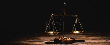 Photo pour Echelles dorées sur table en bois sur fond noir - image libre de droit