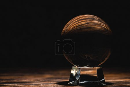 Photo pour Crystal ball on wooden table on black background - image libre de droit