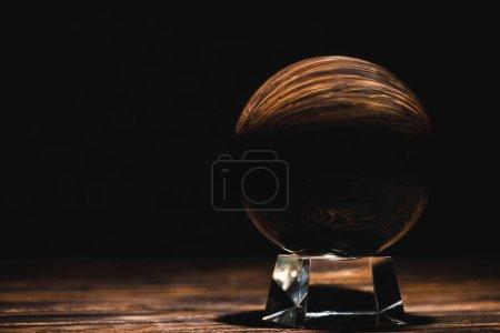 Foto de Crystal ball on wooden table on black background - Imagen libre de derechos