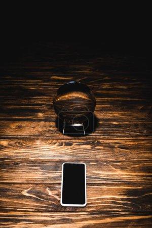 Photo pour Boule de cristal avec smartphone sur table en bois sur fond noir - image libre de droit