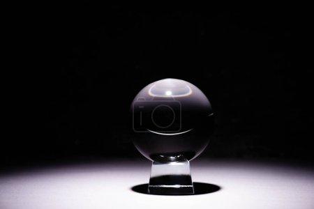 Foto de Crystal ball on white surface on black background - Imagen libre de derechos