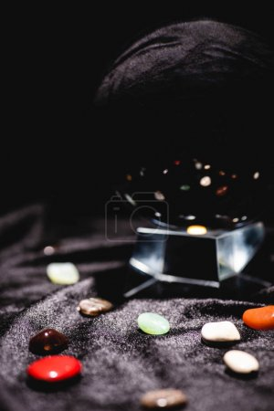 Photo pour Close up view of crystal ball with fortune telling stones on black velvet cloth - image libre de droit