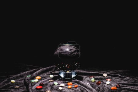 Photo pour Crystal ball with fortune telling stones on black velvet cloth isolated on black - image libre de droit