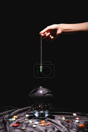 Photo pour Cropped view of fortuneteller holding stone above crystal ball with fortune telling stones on black velvet cloth isolated on black - image libre de droit