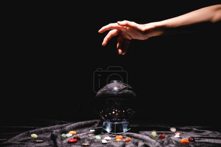 Foto de Cropped view of fortuneteller hand above crystal ball with fortune telling stones on black velvet cloth isolated on black - Imagen libre de derechos