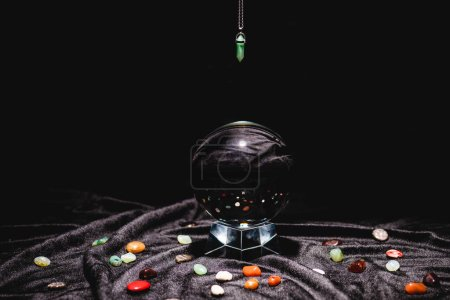 Photo pour Fortune telling stone above crystal ball on black velvet cloth isolated on black - image libre de droit