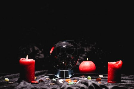 Photo pour Crystal ball with fortune telling stones and candles on black velvet cloth - image libre de droit