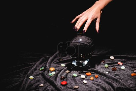 Photo pour Cropped view of fortuneteller hand above crystal ball with fortune telling stones on black velvet cloth isolated on black - image libre de droit