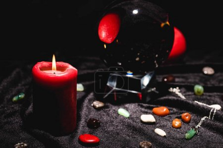 Photo pour Selective focus of crystal ball with fortune telling stones and candle on black velvet cloth - image libre de droit