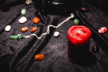 Photo pour Selective focus of fortune telling stones and candle on black velvet cloth - image libre de droit