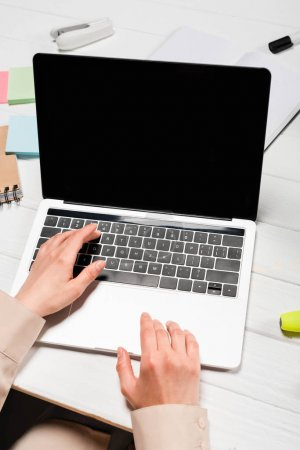 Photo pour Cropped view of woman using laptop at workplace with office supplies - image libre de droit