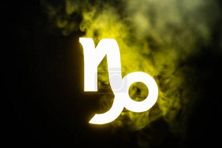 Foto de Yellow illuminated Capricorn zodiac sign with smoke on background - Imagen libre de derechos