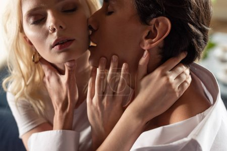 Man touching by neck and kissing beautiful blonde woman