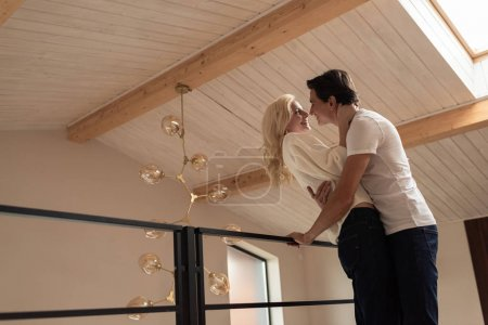 Photo for Side view of smiling couple hugging at balcony - Royalty Free Image