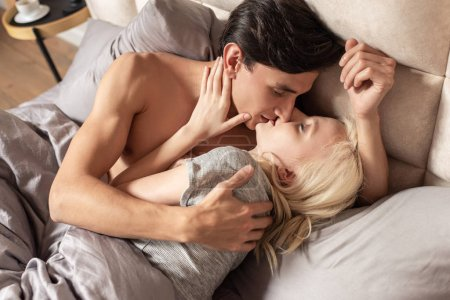 Photo pour Top view of young couple embracing and kissing in bed - image libre de droit
