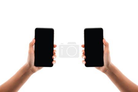Photo pour Vue recadrée de femme tenant des smartphones isolés sur blanc - image libre de droit