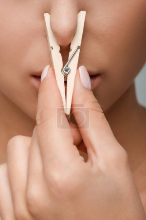 Photo pour Vue recadrée d'une jeune femme touchant une épingle en bois près du nez - image libre de droit