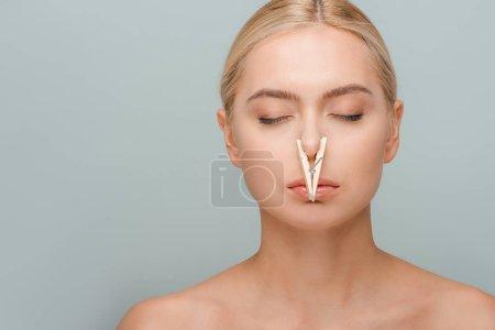 Photo pour Jolie jeune femme nue avec une épinglette en bois sur le nez et les yeux fermés isolée sur le gris - image libre de droit