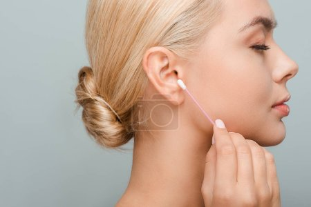 Photo for Side view of woman holding ear stick isolated on grey - Royalty Free Image