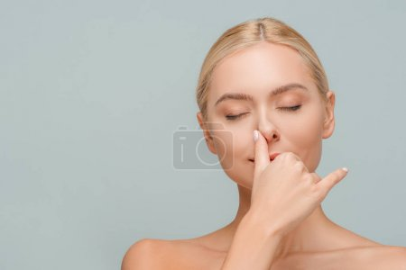 Photo pour Attractive girl with closed eyes touching nose isolated on grey - image libre de droit