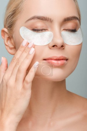 Photo for Attractive woman with eye patches touching face isolated on grey - Royalty Free Image