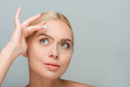 Photo pour Attrayant femme appliquant crème visage isolé sur gris - image libre de droit