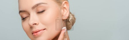Photo pour Panoramic shot of happy woman applying face cream isolated on grey - image libre de droit