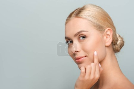 Photo pour Young beautiful woman looking at camera and touching face isolated on grey - image libre de droit