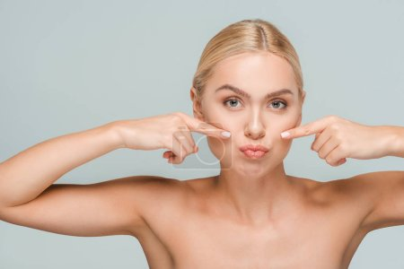 Photo pour Naked woman pointing with fingers at clean face isolated on grey - image libre de droit