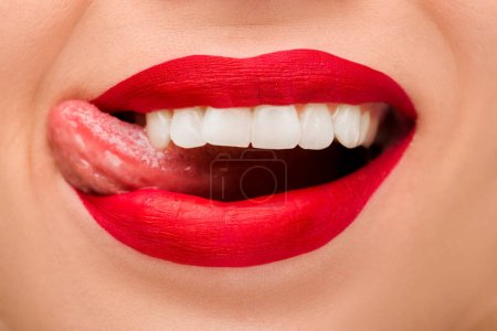 Photo pour Cropped view of cheerful woman with red lipstick sticking out tongue isolated on white - image libre de droit