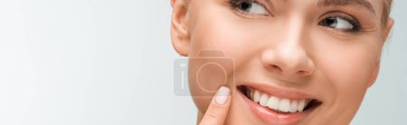 Photo pour Panoramic shot of happy woman pointing with finger at face isolated on white - image libre de droit